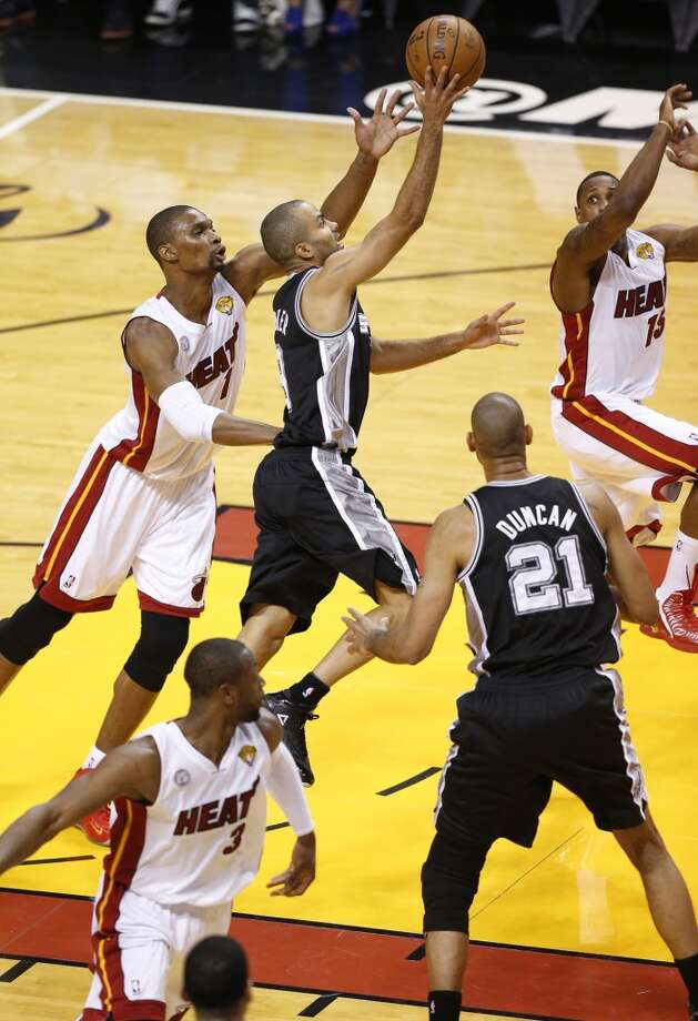 Spurs' Tony Parker (09) drives for a layup against Miami Heat's Chris Bosh (left) and Mario Chalmers (15) during Game 1 of the 2013 NBA Finals Thursday June 6, 2013 at American Airlines Arena in Miami, Fla.