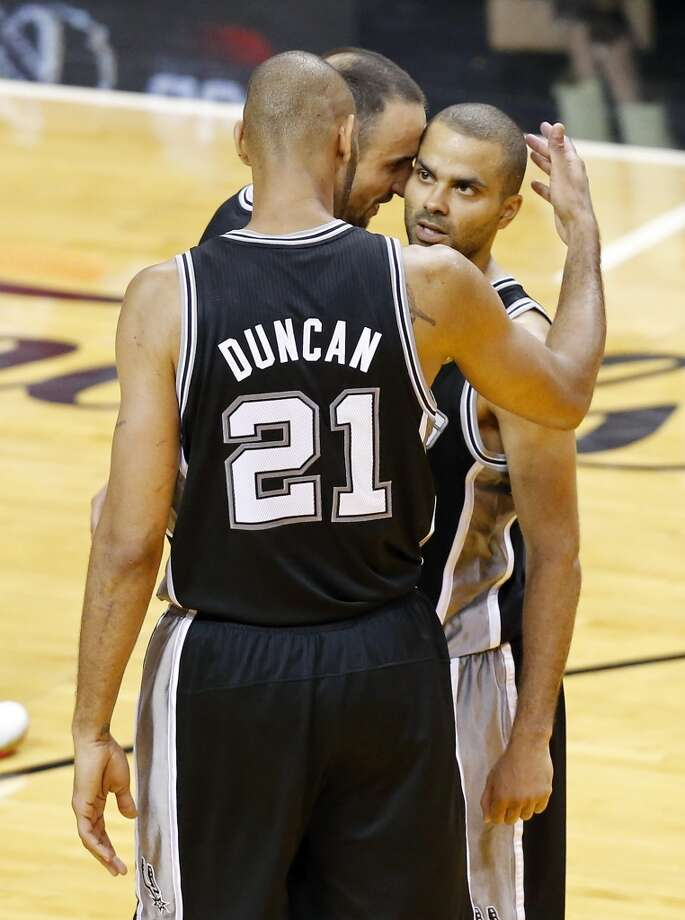 San Antonio Spurs' Manu Ginobili and San Antonio Spurs' Tim Duncan hug teammate San Antonio Spurs' Tony Parker after Game 1 of the 2013 NBA Finals against the Miami Heat Thursday June 6, 2013 at American Airlines Arena in Miami, Fla. The Spurs won 92-88.
