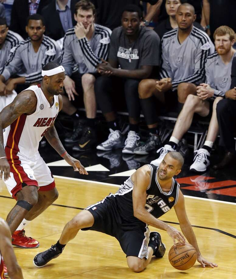 San Antonio Spurs' Tony Parker slips as Miami Heat's LeBron James looks on late in second half action in Game 1 of the 2013 NBA Finals Thursday June 6, 2013 at American Airlines Arena in Miami, Fla. The Spurs won 92-88.