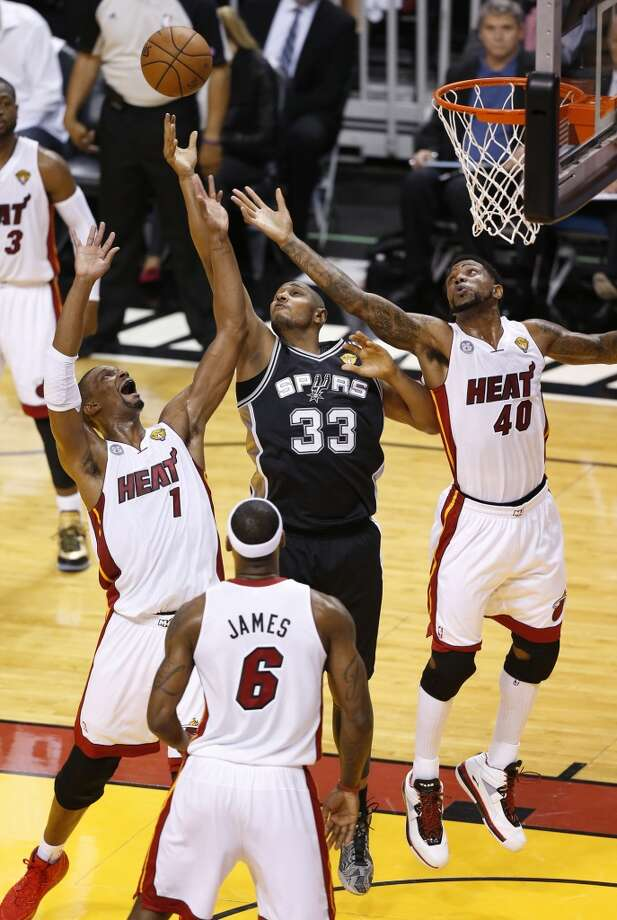 Spurs' Boris Diaw (33) goes up for a rebound against Miami Heats' Chris Bosh (01) and Udonis Haslem (40)during Game 1 of the 2013 NBA Finals Thursday June 6, 2013 at American Airlines Arena in Miami, Fla.