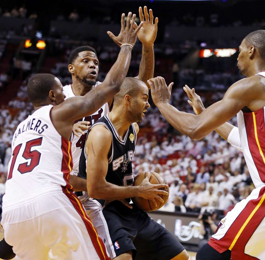 San Antonio Spurs' Tony Parker looks for room between Miami Heat's Mario Chalmers, Miami Heat's Udonis Haslem, and Miami Heat's Chris Bosh in the second half of Game 1 of the 2013 NBA Finals Thursday June 6, 2013 at American Airlines Arena in Miami, Fla.