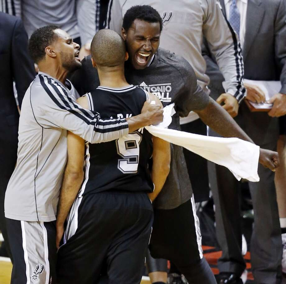 San Antonio Spurs' Tony Parker celebrates with teammates San Antonio Spurs' Patty Mills and San Antonio Spurs' DeJuan Blair after making a shot late in the second half of Game 1 of the 2013 NBA Finals against the Miami Heat Thursday June 6, 2013 at American Airlines Arena in Miami, Fla. The Spurs won 92-88.