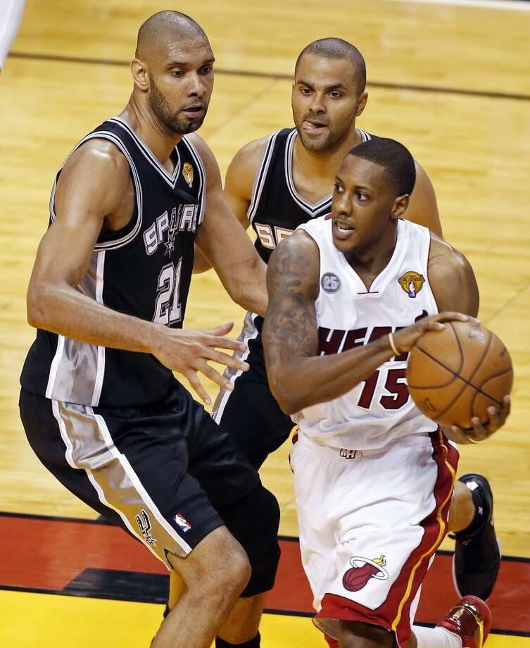 San Antonio Spurs' Tim Duncan and San Antonio Spurs' Tony Parker defend Miami Heat's Mario Chalmers in the second half of Game 1 of the 2013 NBA Finals Thursday June 6, 2013 at American Airlines Arena in Miami, Fla.