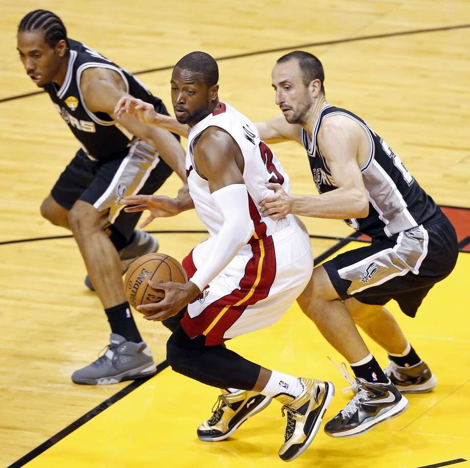 Miami Heat's Dwyane Wade looks for room between San Antonio Spurs' Kawhi Leonard and San Antonio Spurs' Manu Ginobili in the second half of Game 1 of the 2013 NBA Finals Thursday June 6, 2013 at American Airlines Arena in Miami, Fla.