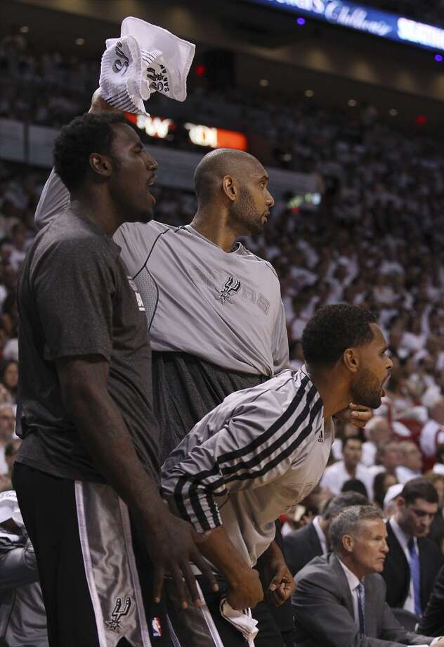 Spurs' DeJuan Blair (45), Patty Mills (08) and Tim Duncan (21) reacts from the bench during the game against the Miami Heat in the second half of Game 1 of the 2013 NBA Finals at the American Airlines Arena in Miami on Thursday, June 6, 2013. Spurs defeated Miami, 92-88. (Kin Man Hui/San Antonio Express-News)