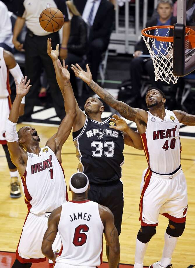 San Antonio Spurs' Boris Diaw grabs for a rebound between Miami Heat's Chris Bosh, Miami Heat's Udonis Haslem and Miami Heat's LeBron James during first half action in Game 1 of the 2013 NBA Finals Thursday June 6, 2013 at American Airlines Arena in Miami, Fla.