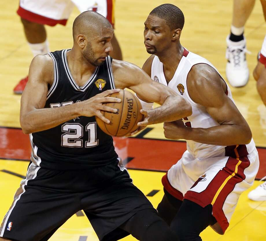 San Antonio Spurs' Tim Duncan looks for room around Miami Heat's Chris Bosh during first half action in Game 1 of the 2013 NBA Finals Thursday June 6, 2013 at American Airlines Arena in Miami, Fla.