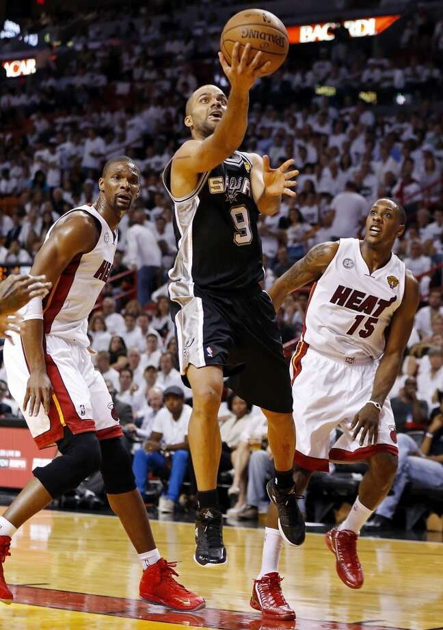 San Antonio Spurs' Tony Parker drives to the basket between Miami Heat's Chris Bosh and Miami Heat's Mario Chalmers in the second half of Game 1 of the 2013 NBA Finals Thursday June 6, 2013 at American Airlines Arena in Miami, Fla.