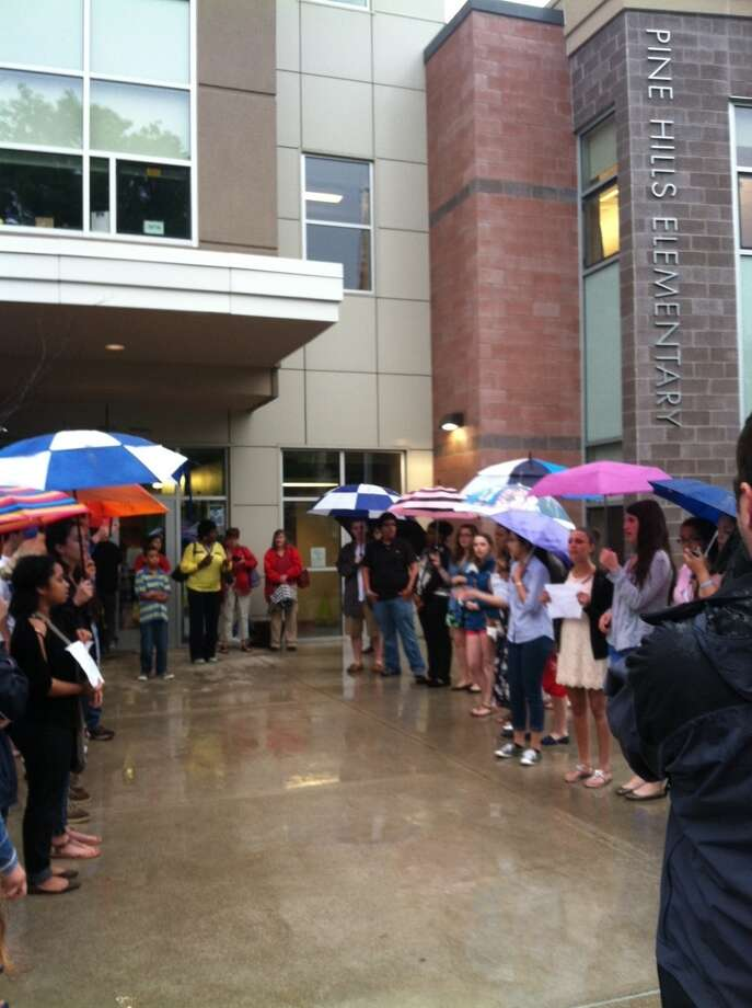 "Albany High School students sing in the rain outside the school board meeting room to show their support for two laid off music teachers on Thursday, June 6. One of their selections was ""Earth Song,"" by Frank Ticheli. (Scott Waldman / Times Union)"