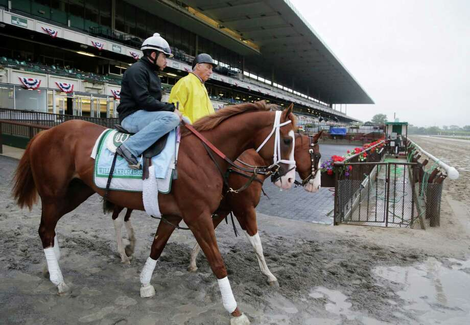 Trainer D. Wayne Lukas leads Will Take Charge, left, onto the track at Belmont Park for a morning workout Friday, June 7, 2013 in Elmont, N.Y. Will Take Charge is entered in Saturday's Belmont Stakes horse race. Photo: Mark Lennihan, AP / AP