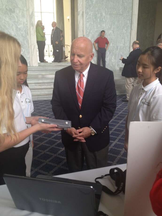 Rep. Kevin Brady listens as the students explain their invention.