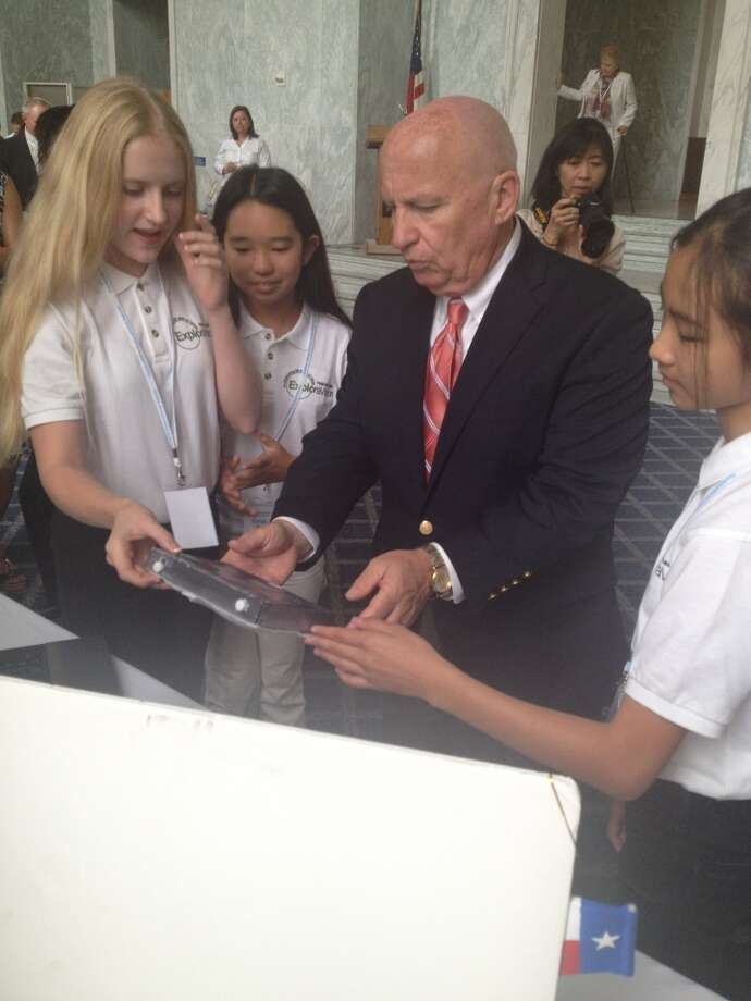 The winning team from The Woodlands, Texas shows Rep. Kevin Brady how their project works.
