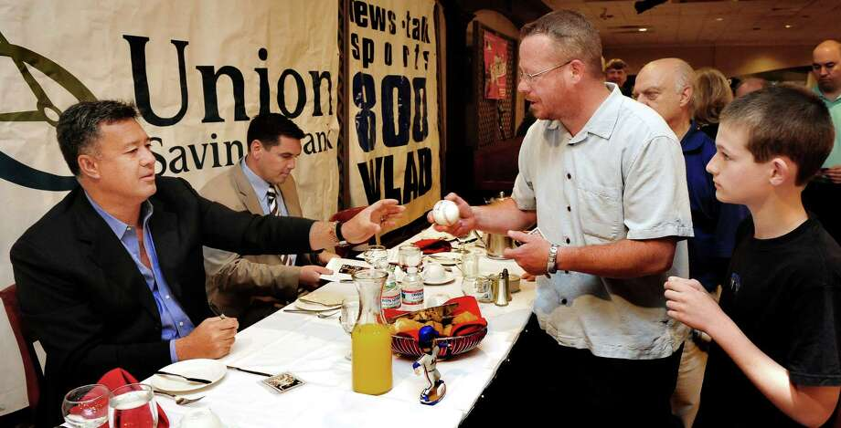 Former New York Met and current SNY announcer Ron Darling, left, is the guest speaker at the Danbury Westerners 19th annual Celebrity Breakfast held at the Amber Room Colonnade in Danbury, Conn. Friday, June 7, 2013. He autographs a baseball for Rick Goodwin and his son, Connor, 12. Photo: Michael Duffy / The News-Times