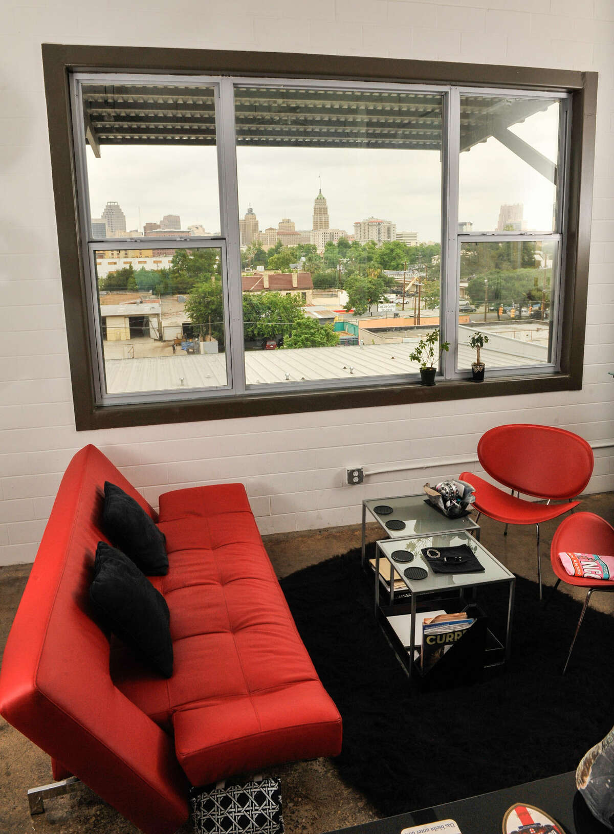 A bright red couch is featured next to a picture window with a downtown view.
