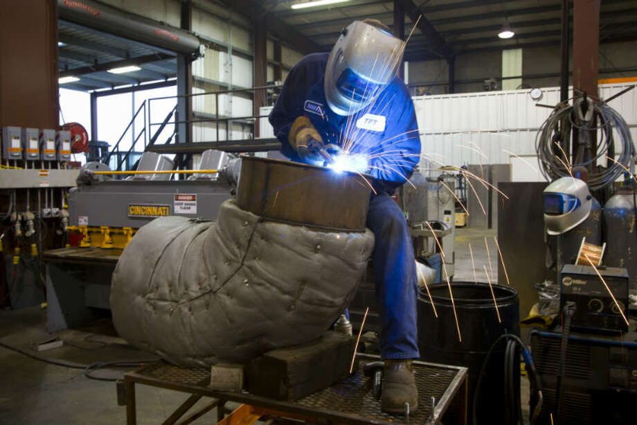 Russell Ashford welds a stainless steel exhaust pipe for a turbine engine at Turbine Power Technology in Franklin, La. ( Brett Coomer / Houston Chronicle )