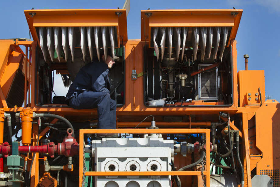 Matt Brown makes adjustments to a turbine engine that powers a hydraulic fracturing unit at Turbine Power Technology in Franklin, La. ( Brett Coomer / Houston Chronicle )