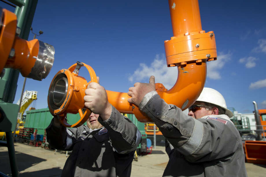Cody Boudreaux (left) and Cheries Burgess, of Green Field Energy Services, adjust a pivoting gas line arm used to fuel hydraulic fracturing units, during a test at Turbine Power Technology in Franklin, La. ( Brett Coomer / Houston Chronicle )