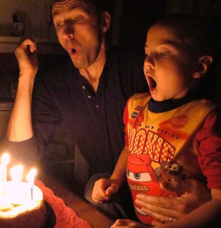Some dads and sons blow out candles together.