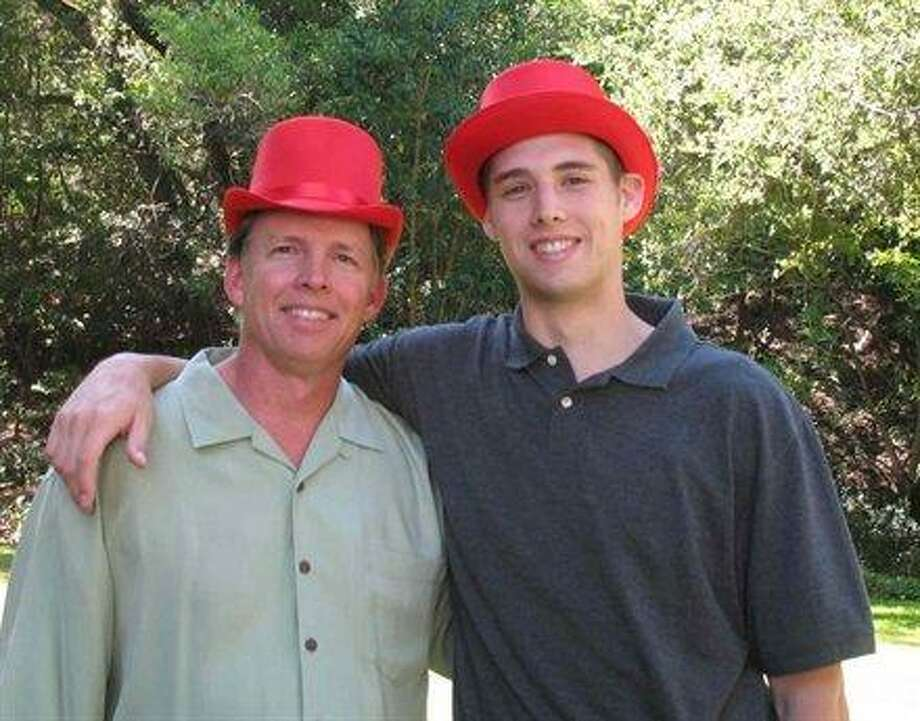 Some fathers and sons have the same red hats.