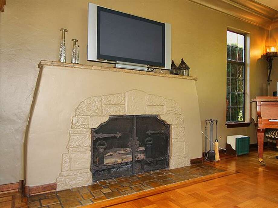 Living room fireplace of 1952 Shenandoah Drive East. The 5,380-squarep-foot house, built in 1928, has five bedrooms, 3.5 bathrooms, a family room with a fireplace, French doors, tile and wood floors, a wine cellar, a terrace and a patio with a fountain on a quarter-acre lot. It's listed for $2.595 million. Photo: Courtesy Adrienne Loop, Windermere Real Estate