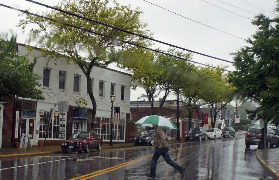 A pedestrian takes cover under and umbrella and dashes across the street Friday in an attempt to stay somewhat dry. Photo: Genevieve Reilly / Fairfield Citizen