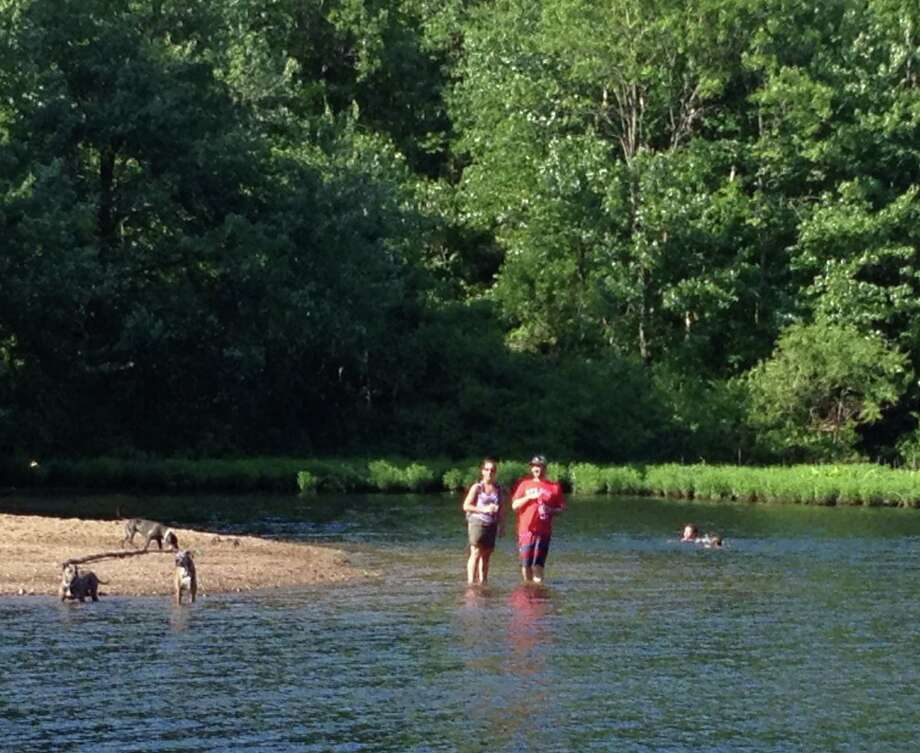 Despite signs warning of the danger, people were seen swimming on a recent Sunday near the same spot at Lake Mohegan where a 10-year-old drowned last July. Swimming is not allowed on the lake's northern end, and violators could be fined $99. Photo: Contributed Photo / Fairfield Citizen