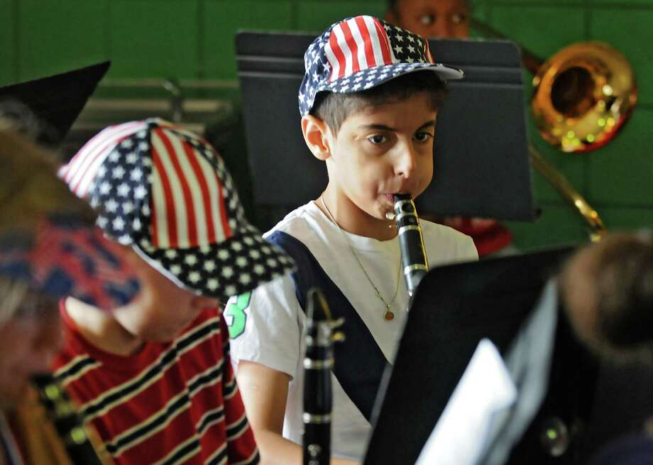 Sina Nakhkoob, age 10, of Troy plays the clarinet in the orchestra at School 14 where the students and teachers were honoring the flag on Friday, June 7, 2013 in Troy, N.Y.(Lori Van Buren / Times Union) Photo: Lori Van Buren / 00022716A