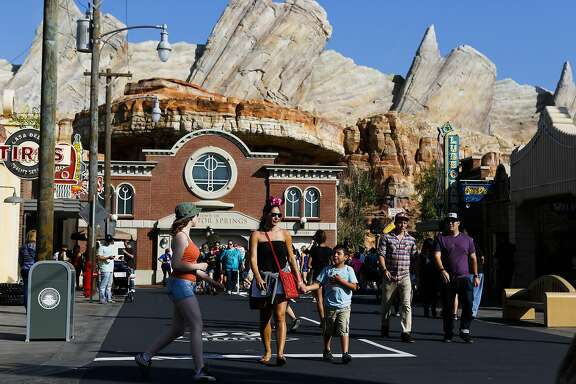 Visitors walk through Cars Land at Walt Disney Co.'s California Adventure Park, part of the Disneyland Resort, in Anaheim, California, U.S., on Friday, May 24, 2013. Walt Disney Co., the world's largest entertainment company, said this month fiscal second-quarter profit rose 32 percent, beating analysts' estimates as guests splurged at theme parks in California and Florida. Photographer: Patrick T. Fallon/Bloomberg