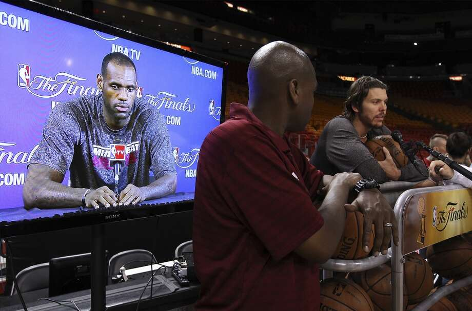Miami Heats' Mike Miller (right) takes questions while teammate LeBron James is shown on a screen during practice and media sessions at the American Airlines Arena in Miami on Friday, June 7, 2013. (Kin Man Hui/San Antonio Express-News)