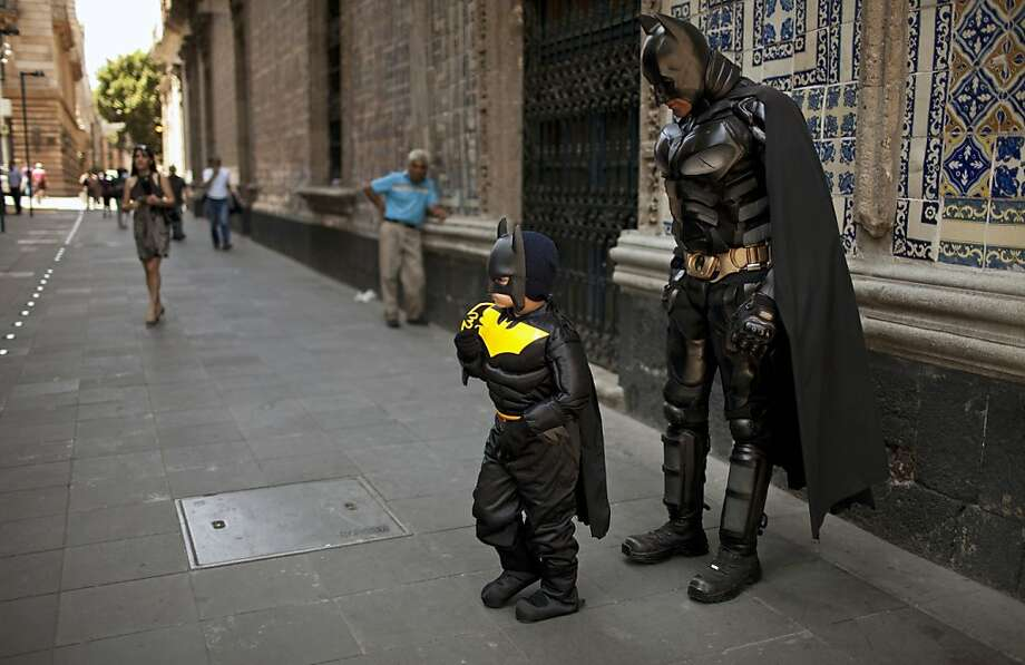A bat and a half: Santiago Gomez, almost 6, received an early birthday gift from his parents - a Batman costume - plus he got to hang out with a Dark Knight street performer in downtown Mexico City. Birthdays don't get much better than that. Photo: Ivan Pierre Aguirre, Associated Press