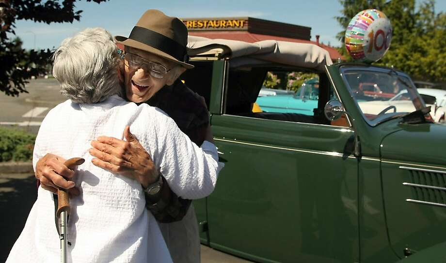 """Still driving his '36 Ford:Charline Austin hugs Bob Bartos on his 100th birthday at the Cool Car Cruz in Bremerton, Wash. Behind him is Bob's 1936 four-door Ford convertible sedan, which he still drives, although not very far. """"I start the motor, back it out of the garage, turn on the radio, listen to it for about 30 minutes and think about the memories."""" Photo: Meegan M. Reid, Associated Press"""