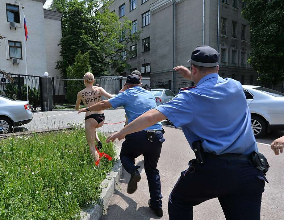 "Topless 'tribute' to Putin: A FEMEN feminist tries to evade arrest in Kiev after she shouted ""Vladimir, I love you!"" and performed an impersonation of Russian rhythmic gymnast Alina Kabayeva with a ribbon. Russian President Vladmir Putin, who announced his divorce this week, has previously been romantically linked with Kabayeva, an Olympian turned legislator 31 years his junior. Photo: Sergei Supinsky, AFP/Getty Images"