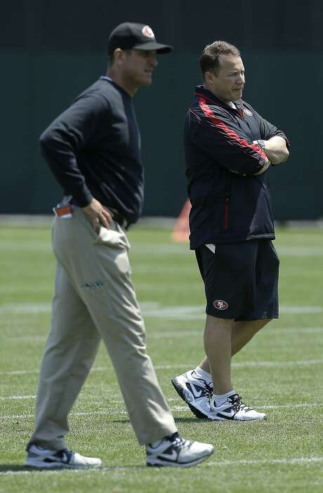 San Francisco 49ers offensive consultant Eric Mangini, right, and head coach Jim Harbaugh watch practice at an NFL football training camp in Santa Clara, Calif., Tuesday, June 4, 2013. (AP Photo/Jeff Chiu) Photo: Jeff Chiu, Associated Press