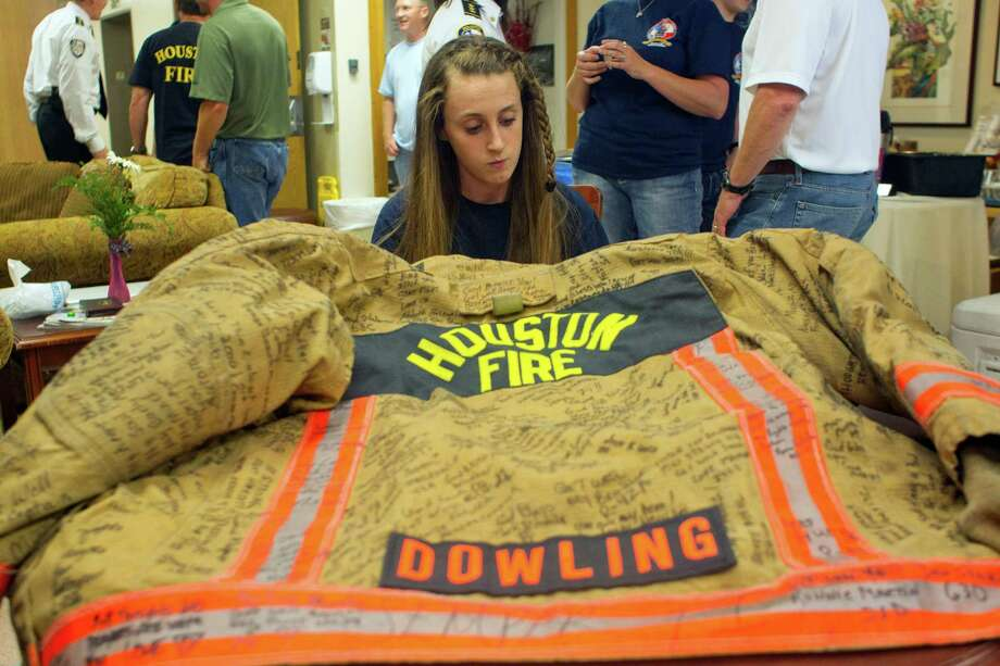 Amid a crowd of well-wishers, Capt. Bill Dowling's daughter, Faith, 13, is drawn to the signatures on his bunker coat. Photo: Johnny Hanson, Staff / © 2013  Houston Chronicle