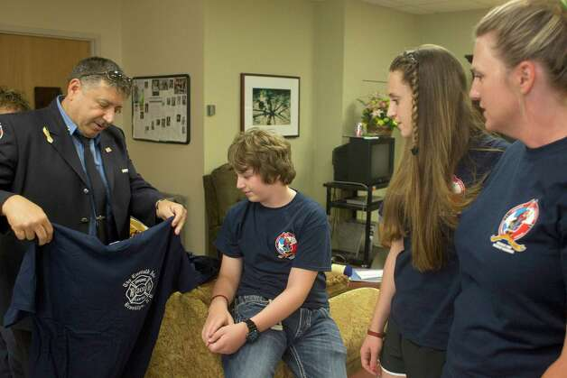 Among this week's stream of visitors to Memorial Hermann Hospital was New York City firefighter Tom Immello, left, who presented a T-shirt to two of Bill Dowling's children, Foster and Faith, and their mom, Jacki. Photo: Johnny Hanson, Staff / © 2013  Houston Chronicle
