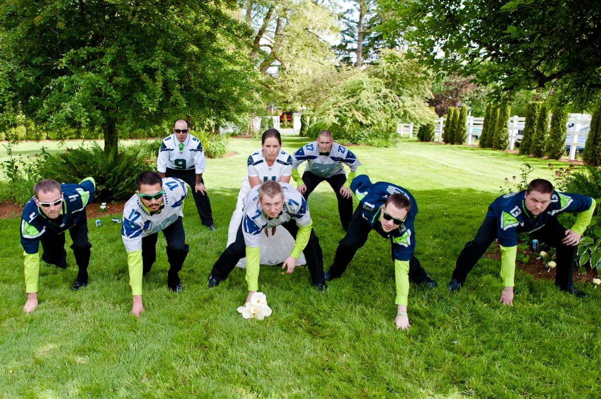 Janna and Ryan Willmaser (''playing'' quarterback and center, respectively) and their groomsmen pose as football players during their Seahawks-themed wedding last weekend at Wine & Roses Country Estate in Auburn.