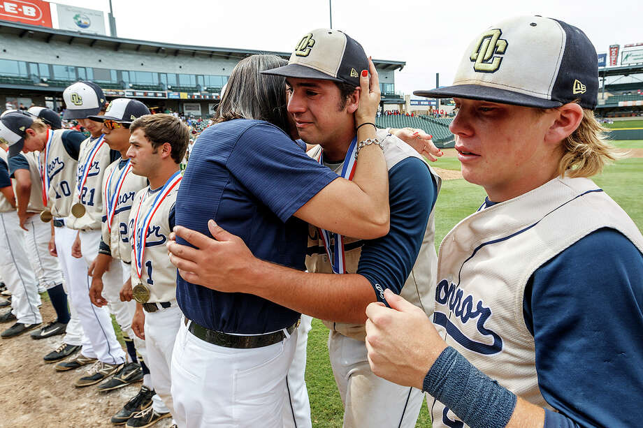 O'Connor's Justin Garcia receives a hug after getting his runner-up medal with Zachary Davenport (right) and the rest of the Panthers following their Class 5A state semifinal game with Conroe The Woodlands at Dell Diamond in Round Rock on Friday, June 7, 2013.  O'Connor lost the game 2-1.   MARVIN PFEIFFER/ mpfeiffer@express-news.net Photo: MARVIN PFEIFFER, Marvin Pfeiffer/ Express-News / Express-News 2013