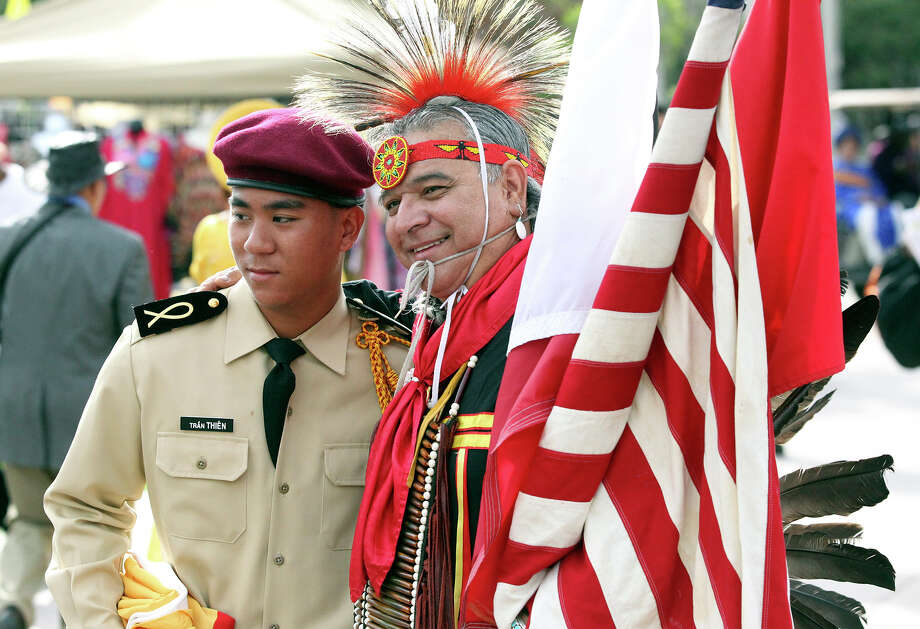 David Tran, in a Vietnamese Military officer's uniform ,gets a picture made with Isaac Cardenas wight he American Indians of Texas as the Texas Folklife Festival opens on the grounds of the Institute of Texan Cultures on June 7, 2013. Photo: TOM REEL