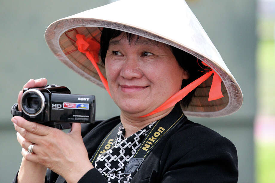 Maria Le operates her video camera while the Vietnamese Community representatives parade as the Texas Folklife Festival opens on the grounds of the Institute of Texan Cultures on June 7, 2013. Photo: TOM REEL