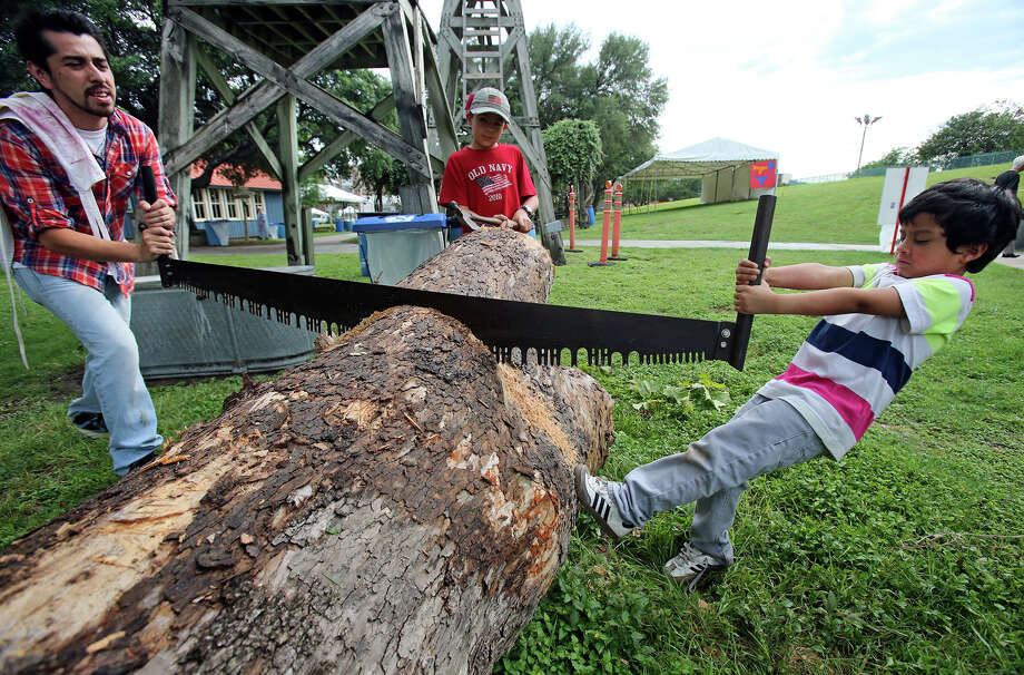 Leotus Vasquez puts his foot into the effort of sawing a tree stump with his dad Javier Vasquez and friend Jarod Wilson as the Texas Folklife Festival opens on the grounds of the Institute of Texan Cultures on June 7, 2013. Photo: TOM REEL