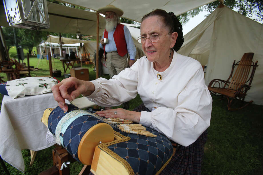 Rita Rice demonstrates a procedure called bobbin lace while Russell Rice settles in for the evening as the Texas Folklife Festival opens on the grounds of the Institute of Texan Cultures on June 7, 2013.  They are with the 173rd New York State Volunteer Infantry displaying in several tents. Photo: TOM REEL