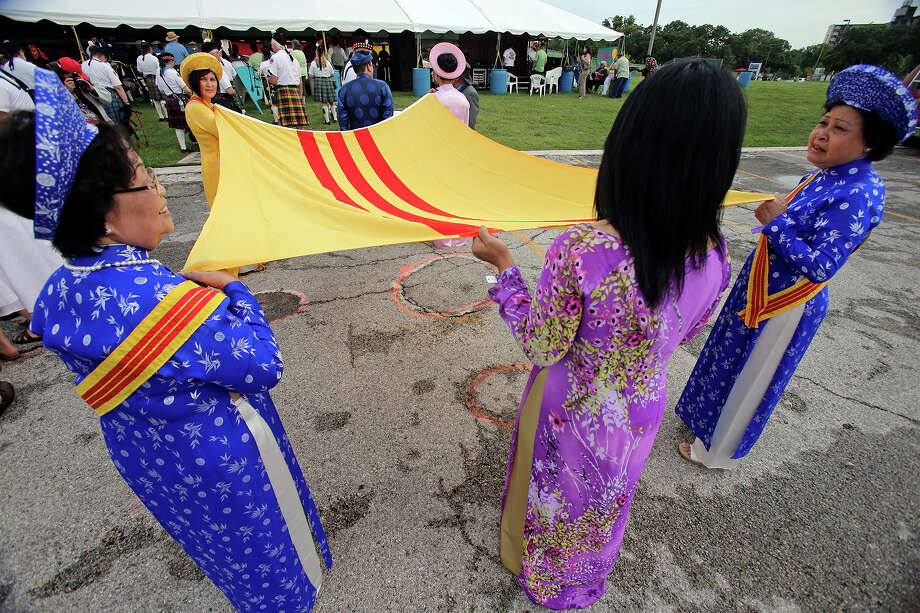 Vietnamese Community members Loe-Nguyen (from left), Amalia Tran and Tam Tran hold the Vietnamese flag as the Texas Folklife Festival opens on the grounds of the Institute of Texan Cultures on June 7, 2013. Photo: TOM REEL