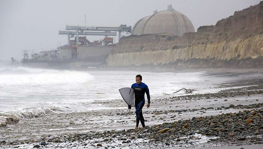With the San Onofre Nuclear Generating Station as a backdrop, Huy Pham of San Juan Capistrano walks south along the beach at San Onofre State Beach early Friday morning, June 7, 2013, after it was announced that the nuclear plant will be closing permanently. (AP Photo/The Orange County Register, Mark Rightmire)   MAGS OUT; LOS ANGELES TIMES OUT Photo: Mark Rightmire, Associated Press
