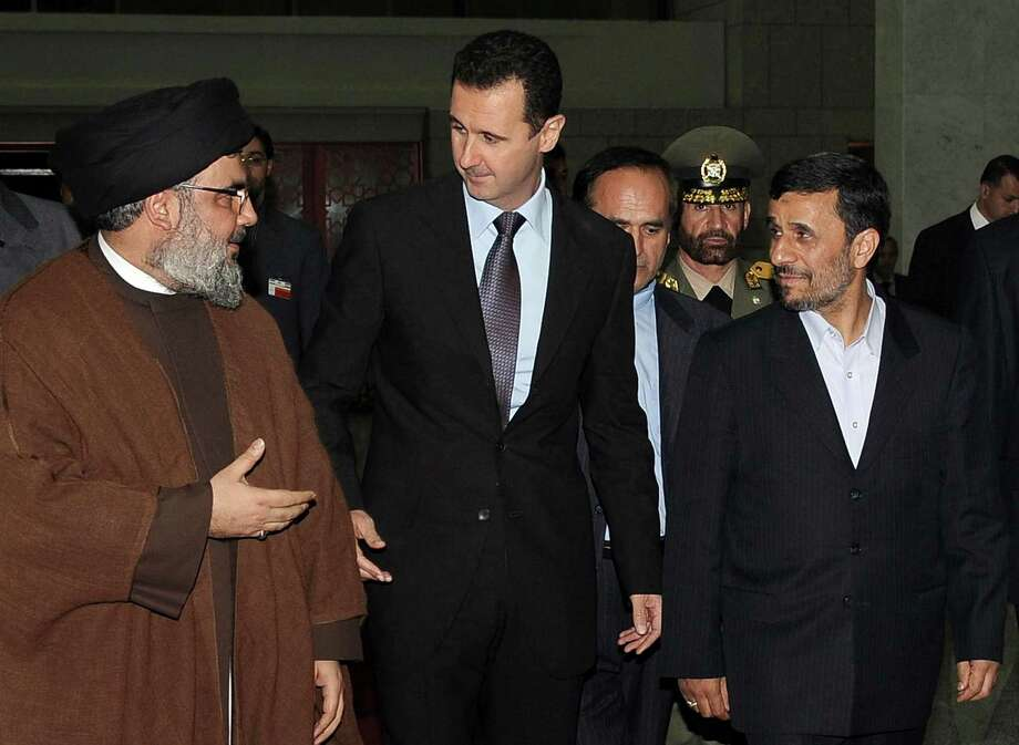 FILE -- In this Thursday February 25, 2010 file photo, released by the Syrian official news agency SANA, Hezbollah leader sheik Hassan Nasrallah, left, speaks with Syrian President Bashar Assad, center, and Iranian President Mahmoud Ahmadinejad, right, upon their arrival for a dinner, in Damascus, Syria. Syria's civil war has morphed into a proxy fight in which Shiite Iran has strongly backed Assad, while Sunni Arab nations have backed rebels. Many Sunni hard-liners around the Mideast have taken Hezbollah's intervention in Syria almost as a declaration of war by Shiites against Sunnis. (AP Photo/SANA, File) Photo: Uncredited, HOPD / SANA