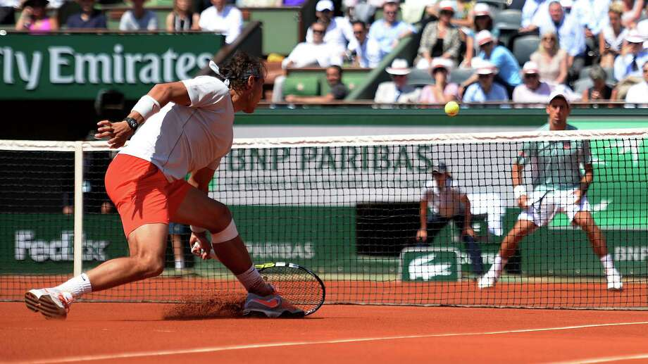 Spain's Rafael Nadal, left, exhibits his knack for prolonging a point by coming to a sliding stop in front of the net and digging a return out of the clay during his five-set French Open semifinal win over Novak Djokovic. Photo: MARTIN BUREAU, Staff / AFP