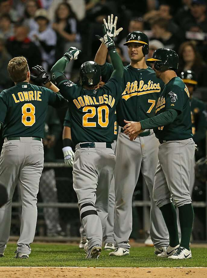 Josh Donaldson is greeted at home plate after hitting his first career grand slam to put the A's ahead of the White Sox in the sixth inning. The A's have won 18 of their last 21. Photo: Jonathan Daniel, Getty Images