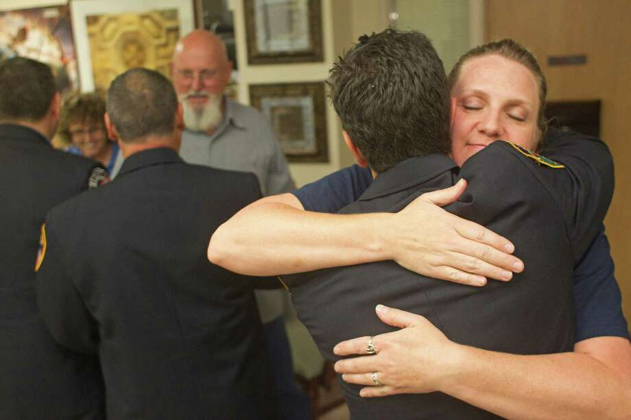 "New York City firefighter, Kevin Selfani from Engine Company 201, gives Jacki Dowling, Capt. William Dowling's wife, a hug as friends and family gathered in the waiting room area in support of  Capt. Dowling at Memorial Hermann Hospital Thursday, June 6, 2013, in Houston. Capt. Dowling is in a medically induced coma since the fire and is listed in critical - but stable - condition. He has had both of his legs partially amputated. Though in a comma, his wife, Jacki said he has responded by ""sticking is tongue out"" when asked to. Photo: Johnny Hanson, Houston Chronicle / © 2013  Houston Chronicle"