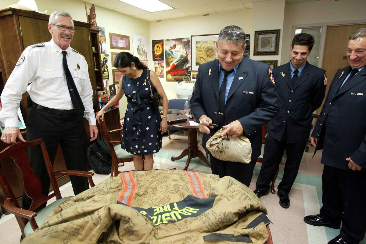 New York City firefighter, Tom Immello from Engine Company 201, signs the fire jacket of Capt. William Dowling next to HFD Chief Terry Garrison, left, and two of his NYFD colleagues as people gathered in the waiting room area in support of Capt. William Dowling at Memorial Hermann Hospital Thursday, June 6, 2013, in Houston.
