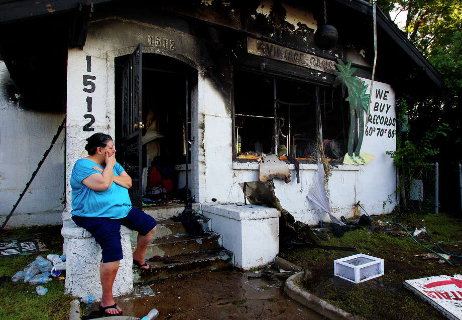 Cher Castro looks at the remains of a fire at her store, Friday, June 7, 2013, in Houston. Castro's store of 18 years, Vintage Oasis, burned last night taking the lives of her two cats and a tenants three cats. Firefighters said that the fire started in the back room. Photo: Cody Duty, Houston Chronicle / © 2013 Houston Chronicle