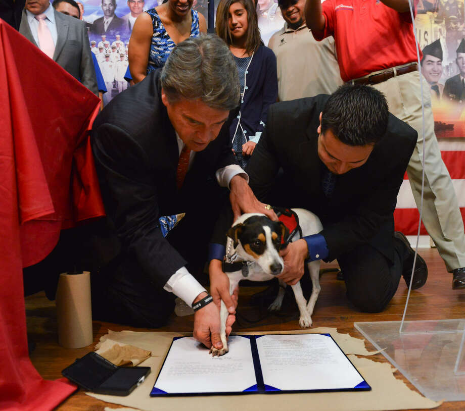 Gov. Rick Perry and former Army Spc. Adan Gallegos help Gallegos' dog, Boots, sign legislation which will allow people with disabilities to use the assistance of service animals in all public places. Photo: Robin Jerstad / Special To The San Antonio Express-News